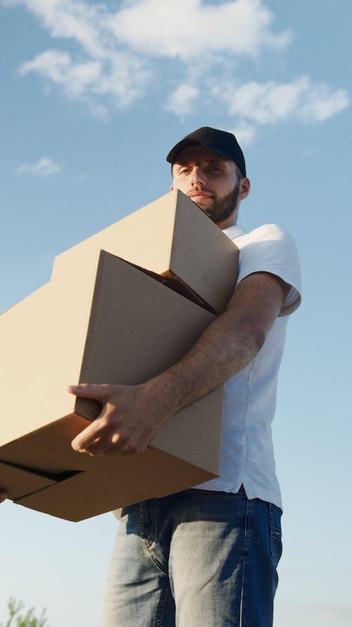 Man in White T-shirt Holding White Box