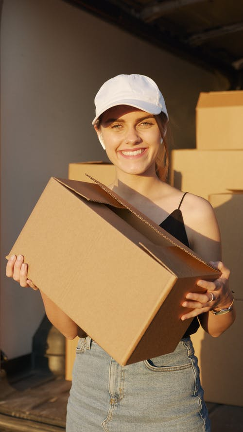 Woman Smiling while Holding a Box
