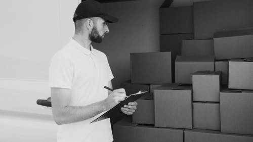 Grayscale Photo of Man Looking at Boxes