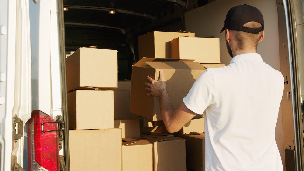 Man in White T-shirt Holding Brown Cardboard Boxes