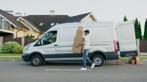 Man in White T-shirt and Blue Denim Jeans Standing Beside White Van