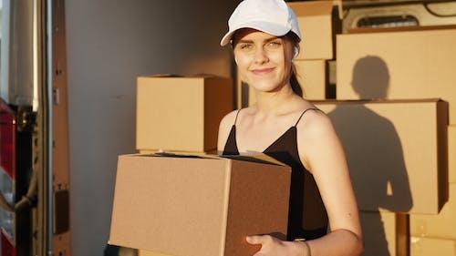 Woman in Black Tank Top Holding Brown Cardboard Box