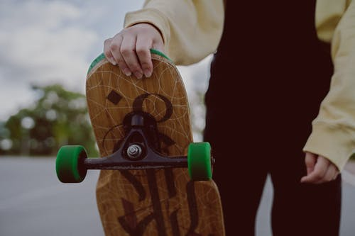 Close-Up Photo of a Person's Hand Holding a Longboard