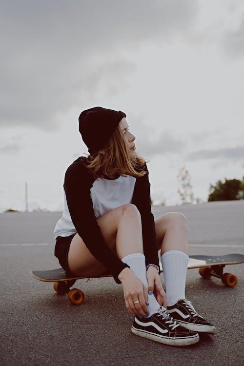Женщина в черной рубашке с длинным рукавом и белых штанах сидит на коричневой деревянной скамье
