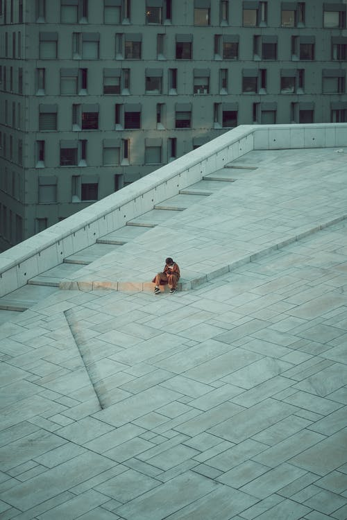 Woman in Brown Coat Sitting on White Concrete Floor