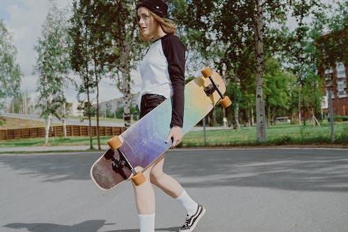 道路に立っている白い長袖シャツと青いスカートの女性