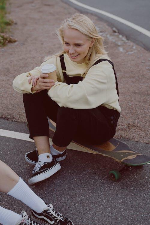 Женщина в белой рубашке с длинным рукавом и черной юбке сидит на коричневом скейтборде