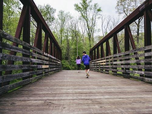 Man in Blue Shirt and Black Shorts Walking on Wooden Bridge