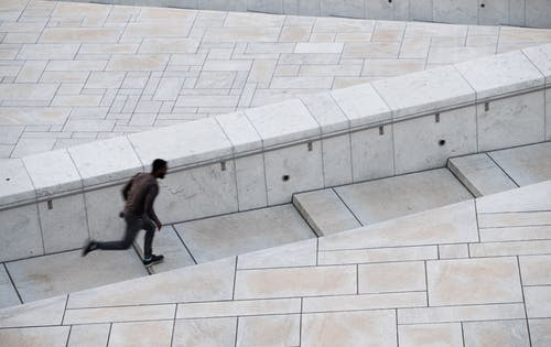 Man in Black Jacket Sitting on White Concrete Bench