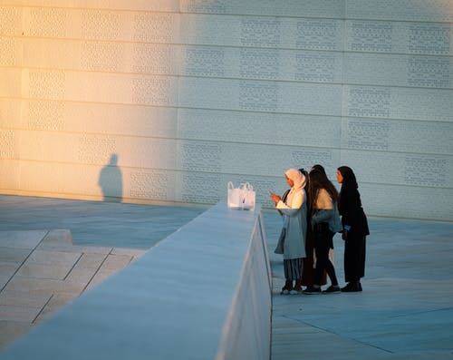 Man and Woman Sitting on Gray Concrete Bench