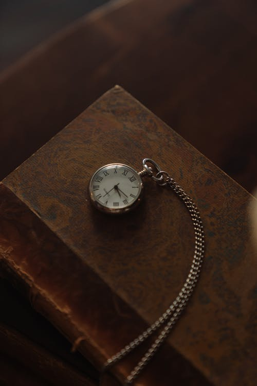 Silver Pocket Watch on Brown Wooden Table