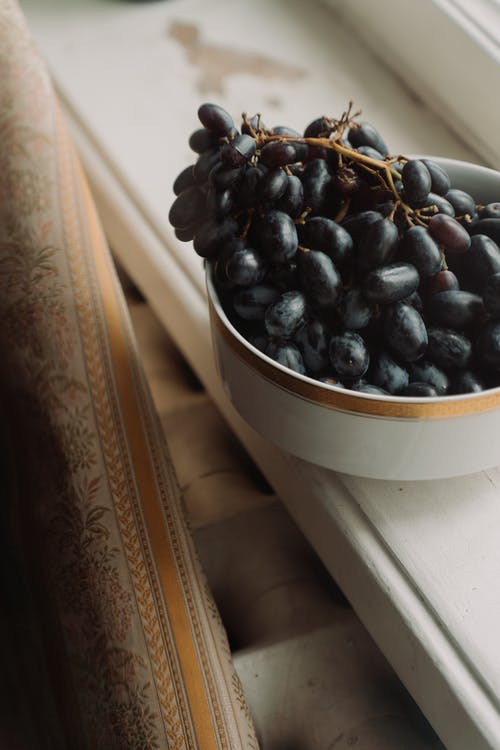 Black Round Fruit on White Ceramic Bowl