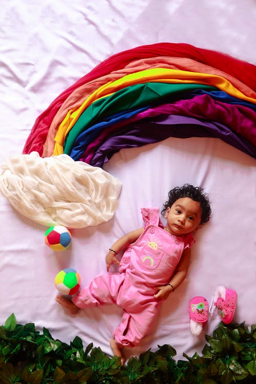 Baby in Pink Onesie Lying on Bed