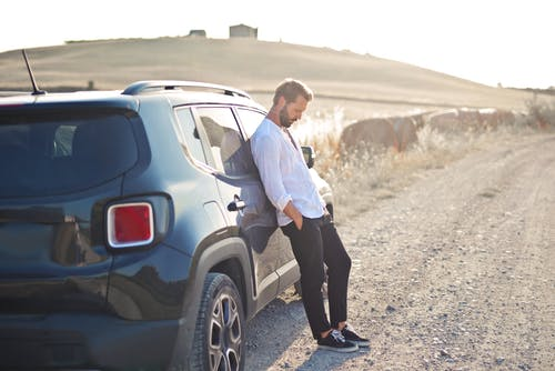 Man in White Dress Shirt and Black Pants Standing Beside Silver Suv