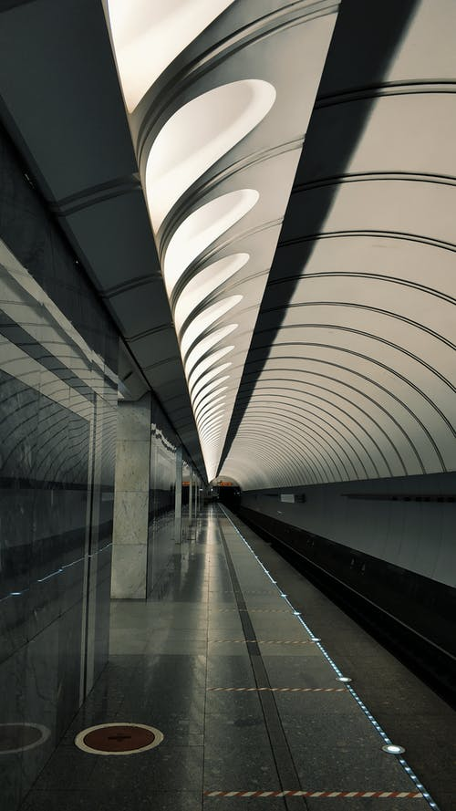 Perspective view of long empty platform of subway station with modern design without train