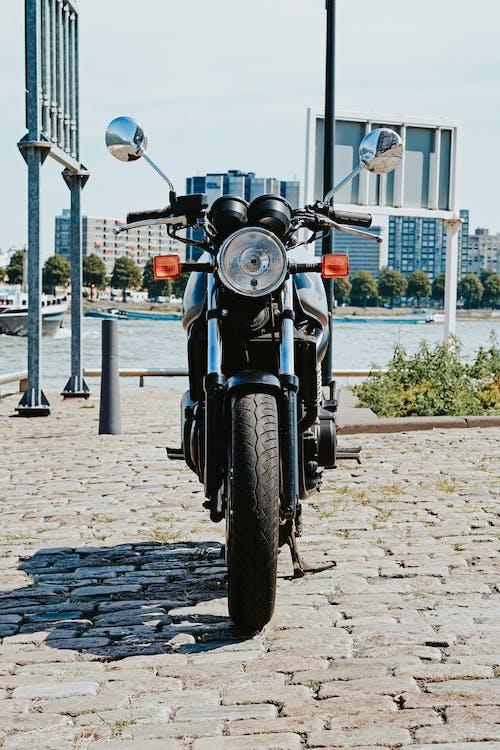 Black Motorcycle Parked Beside Black Metal Fence