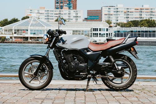 Black and Silver Cruiser Motorcycle Parked on Gray Concrete Pavement