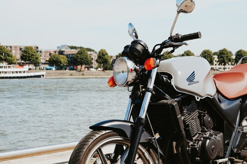 White and Black Motorcycle Near Body of Water