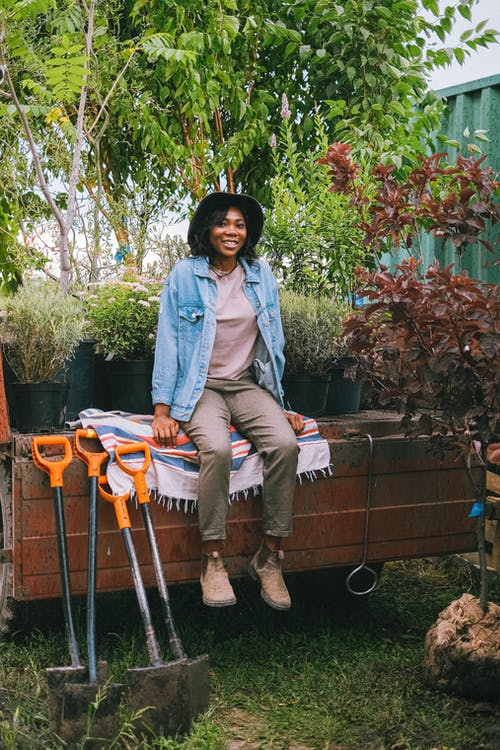 Woman in Blue Denim Jacket and Brown Pants Sitting on Brown Wooden Crate