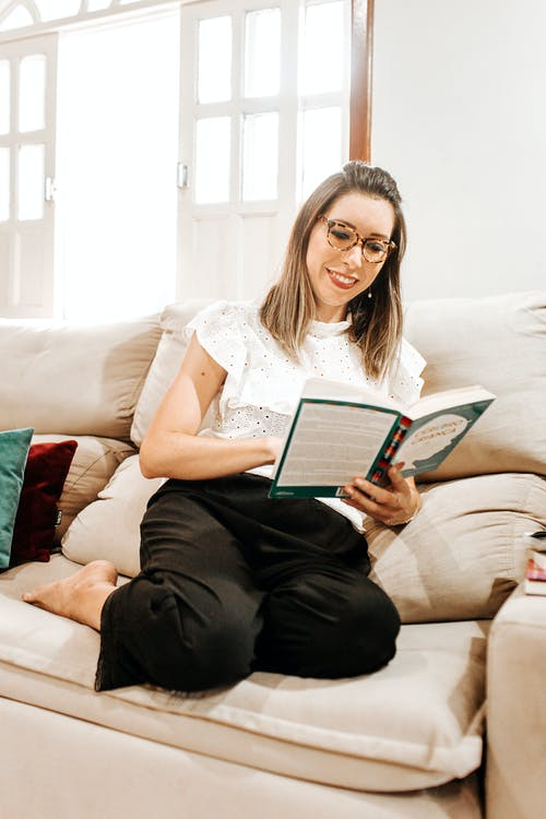 Positive young female in casual clothes and eyeglasses sitting on comfortable sofa and reading interesting book at home