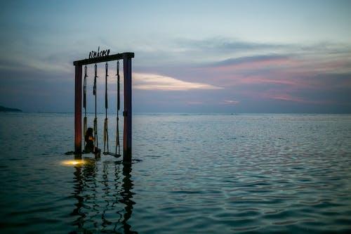 Faceless traveler on swing in sea at sunset