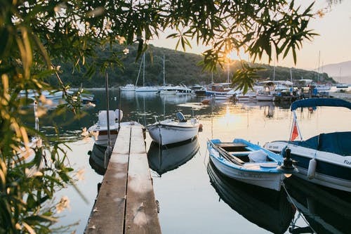 Moored boats in bay at sunset