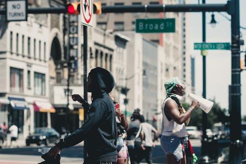 Faceless demonstrators on street in city in summertime
