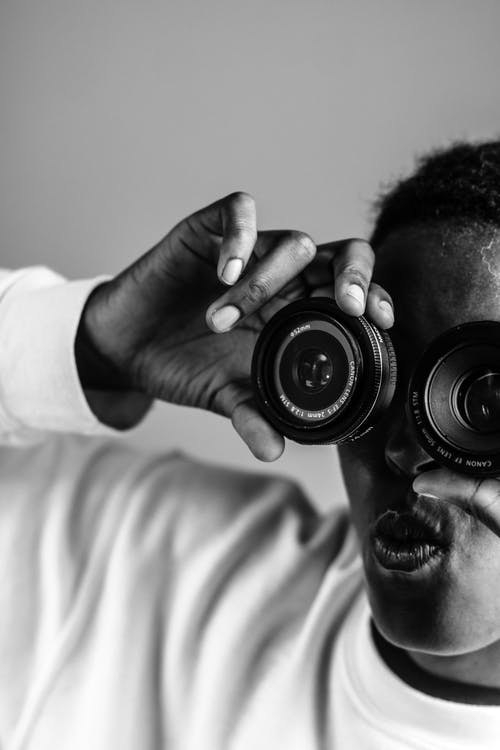 Black photographer looking through lenses