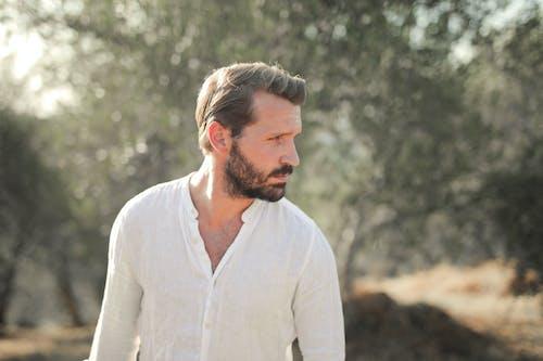 Man in White Dress Shirt Standing Near Green Trees