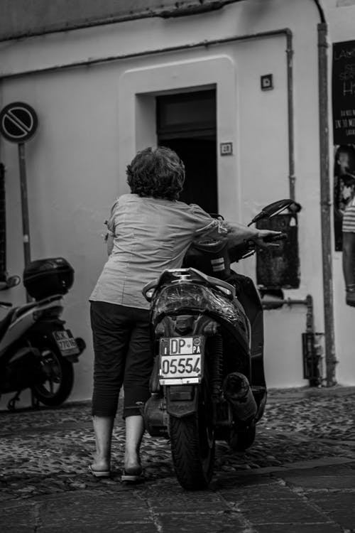 Black and white of unrecognizable female in casual clothes parking motorbike on street in daytime