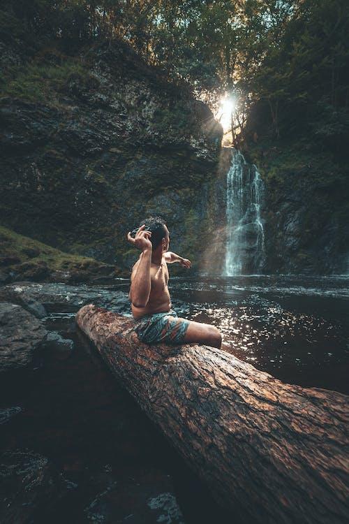 Woman in Black Bikini Sitting on Brown Rock Near Waterfalls