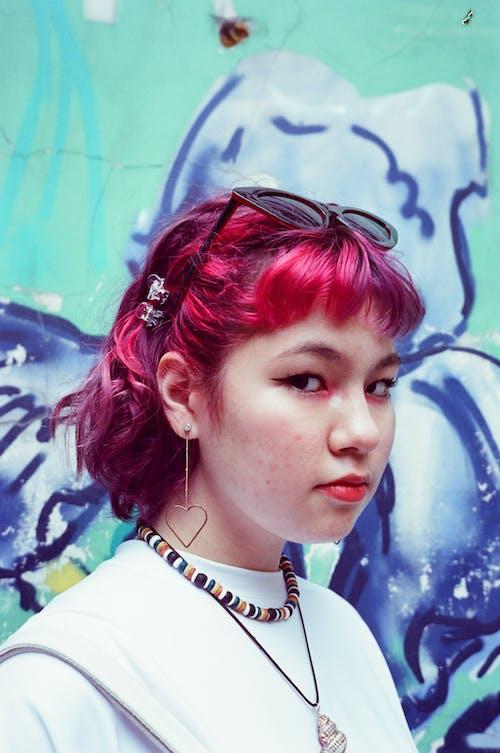 Pensive informal ethnic teen girl against graffiti wall