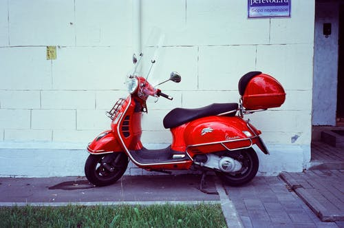 Red and Black Motor Scooter Parked Beside White Wall
