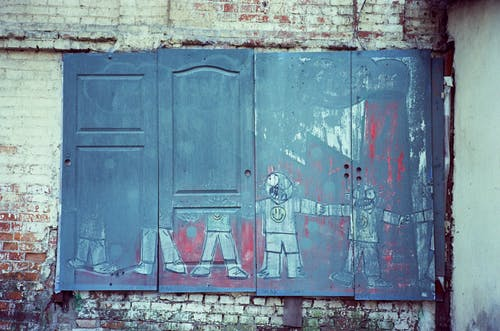 Shabby wooden door with graffiti on weathered stone wall