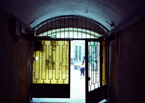 Half opened gate with glass windows of old passage leading to city street in daylight