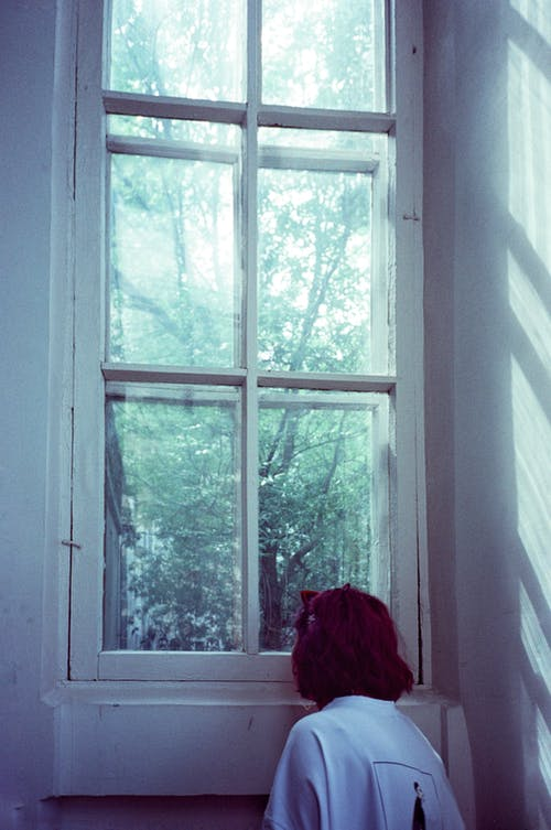 Anonymous woman standing near window overlooking forest