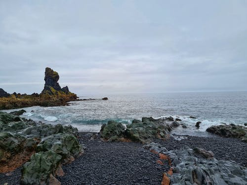 Shoreline with wet rocky formations and small stones located near stormy sea with foamy waves on cloudy day