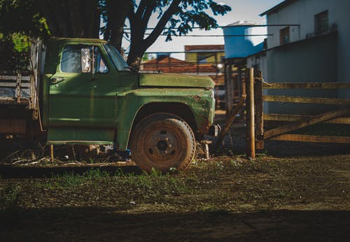 Old pickup truck parked on yard near house