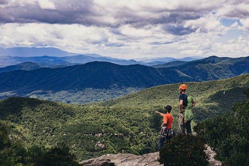 2 Men Standing on Rock Mountain