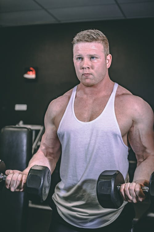 Strong sportsman working out with dumbbells in gym