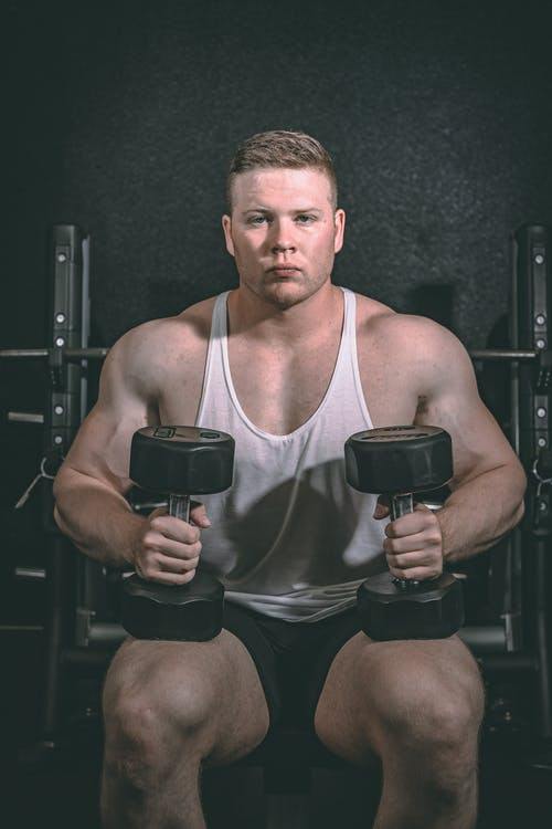 Concentrated bodybuilder with muscles working out with dumbbells in gymnasium