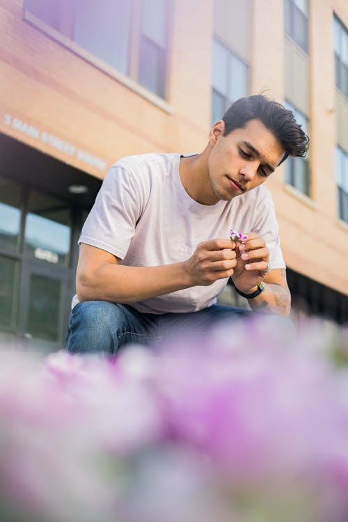 Stylish pondering man contemplating flower on street