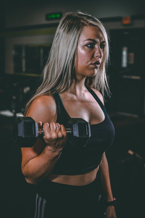 Focused sportswoman exercising with dumbbells in gymnasium