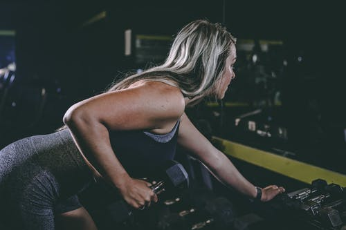 Side view of anonymous young sportswoman in active wear doing dumbbell row while exercising in gym and looking forward