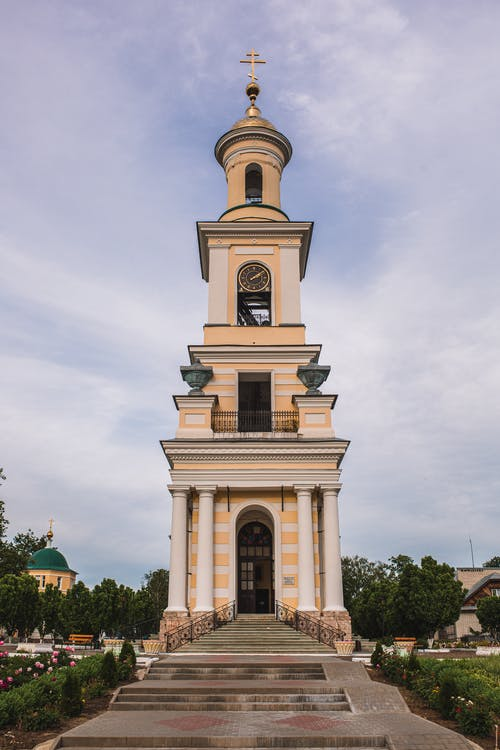 Exterior of ancient church tower with golden cross over old clock and white columns behind stone stairs in daylight