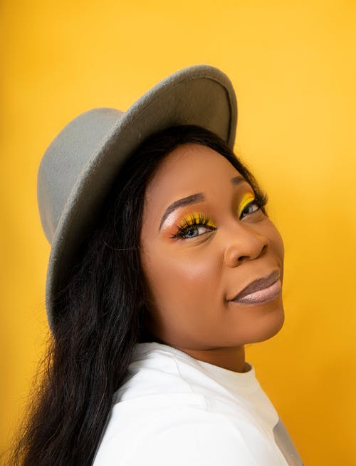 Stylish black woman with colorful makeup in hat