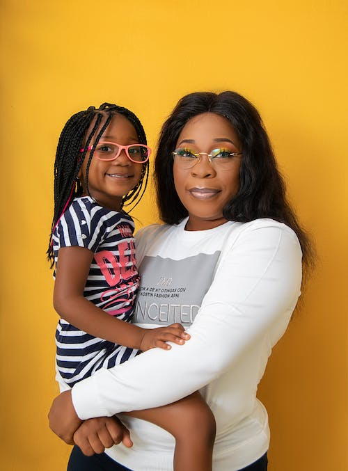 Smiling African American woman with bright makeup holding in arms cute child while standing in bright yellow studio
