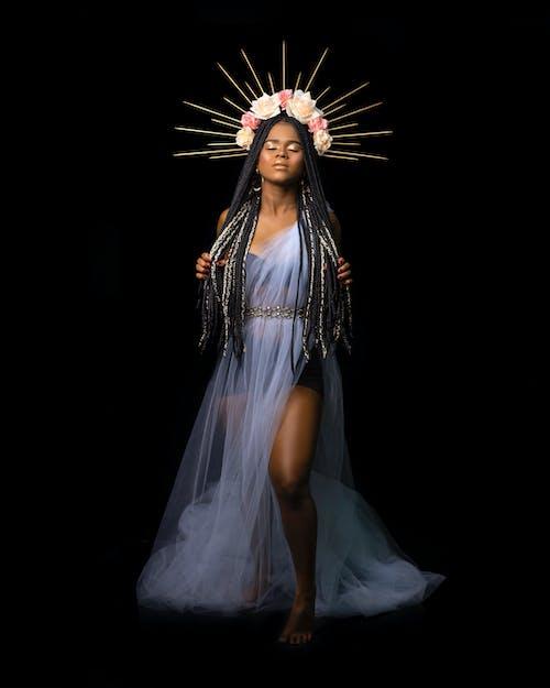 Elegant ethnic woman with dreadlocks in studio
