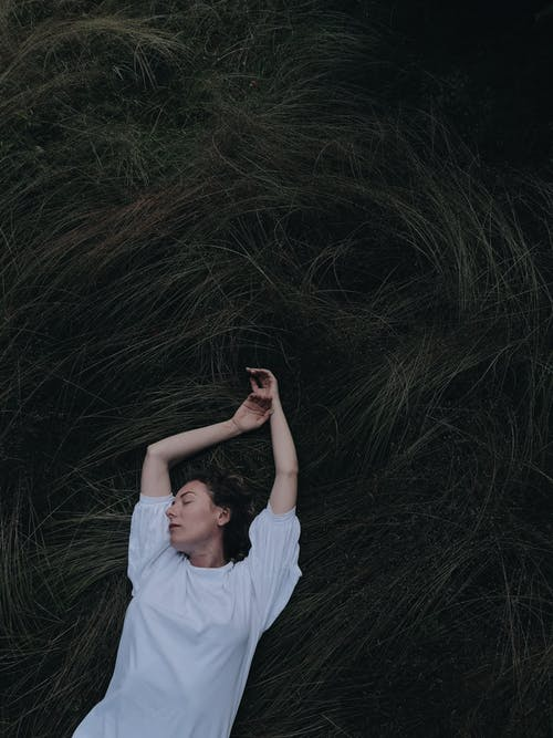 Man in White T-shirt Lying on Grass Field