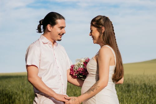Man in White Button Up Shirt Holding Bouquet of Flowers Beside Woman in White Sleeveless Dress